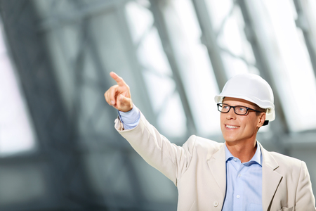 agreeable: Have a glance. Agreeable professional architect holding his hand up a pointing while evincing joy Stock Photo