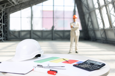 architect tools: Always ready to work. Selective focus of tools for work lying on the table with professional architect standing on the background Stock Photo