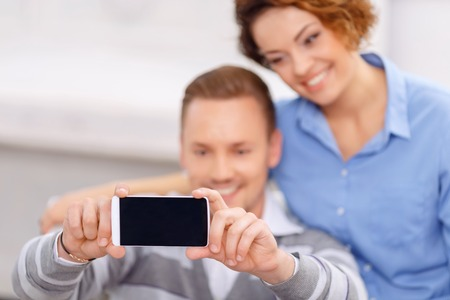 say cheese: Say cheese. Close up of mobile phone in hands of pleasant handsome cheerful man holding it and making photos with his girlfriend