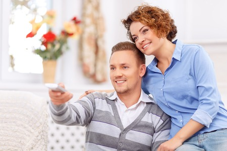 agreeable: Cozy evening. Agreeable young cheerful couple bonding to each other and expressing love while watching TV