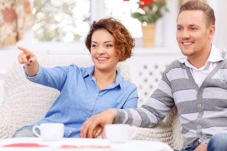 upbeat: Have a look. Overjoyed upbeat young couple sitting in the armchairs and drinking tea while expressing gladness