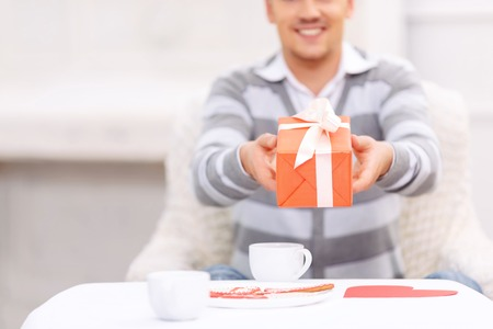 agreeable: Here you are. Agreeable handsome young man holding presenting gift and having dinner while sitting at the table