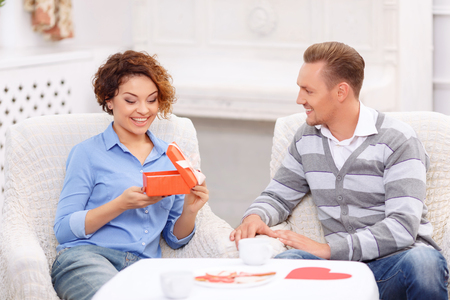 contented: What a surprise. Nice contented emotional girl opening present and showing wonder while sitting at the table with her boyfriend Stock Photo