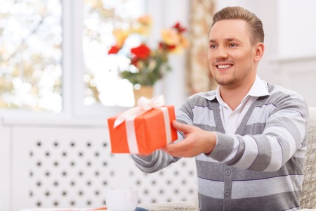 blissful: Want to make you happy. Blissful handsome young man presenting gift and having cozy dinner
