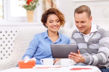 agreeable: Surf the Internet. Positive delighted young couple holding laptop and sitting at the table while having agreeable time
