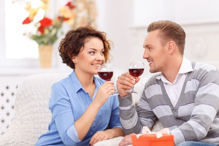upbeat: Pleasant moment. Upbeat happy young couple drinking wine and sitting at the table while looking at each other Stock Photo
