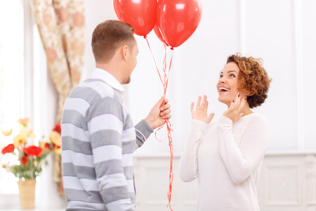 enjoyable: Enjoyable present. Pleasant young handsome guy presenting balloonsto his girlfriend looking surprised