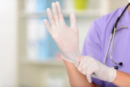 work gloves: Almost ready. Close up of professional young vet wearing gloves and preparing for work Stock Photo