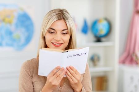 feeling positive: Involved in learning. Agreeable vivacious attractive girl holding dictionary and looking through it while feeling positive Stock Photo