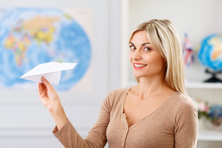 upbeat: Want to fly. Agreeable beautiful upbeat young woman expressing positivity and holding paper plane Stock Photo