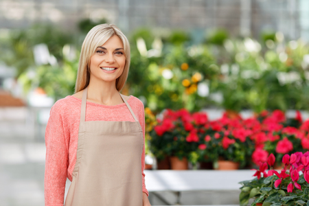 Love my work. Waist up of pleasant charming delighted smiling woman expressing positivity while being involved in work with flowers Stock Photo