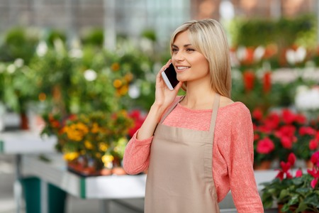 waist up: Nice to hear you. Waist up of nice attractive smiling florist holding mobile phone and having pleasant conversation while working
