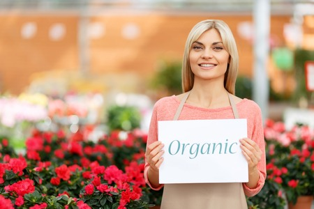 agreeable: Full of positivity. Cheerful smiling agreeable florist holding card and evincing joy while being at work