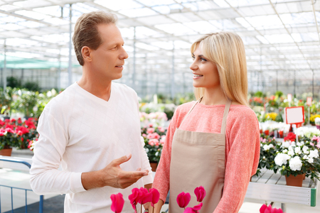 selling service: Good service. Pleasant cheerful professional florist talking with handsome upbeat man while selling flowers