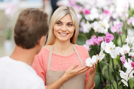 recommending: Choose this one. Pleasant smiling professional florist showing flowers to the customer and recommending while expressing joy