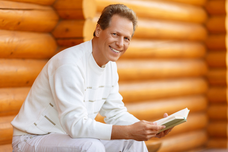 man holding book: Involved in a plot.  Pleasant smart adult man holding book and reading it while having rest