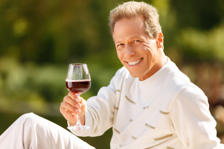 grass beautiful: Cheers. Pleasant handsome blissful man holding glass and drinking wine while evincing positivity
