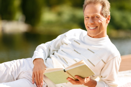 agreeable: Full  of joy. Agreeable handsome  overjoyed man holding book and reading it while  resting on the blanket