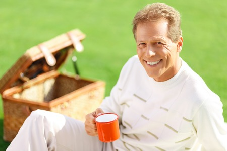cip: Full of positivity. Elated vivacious content man holding cup and drinking tea while expressing gladness Stock Photo