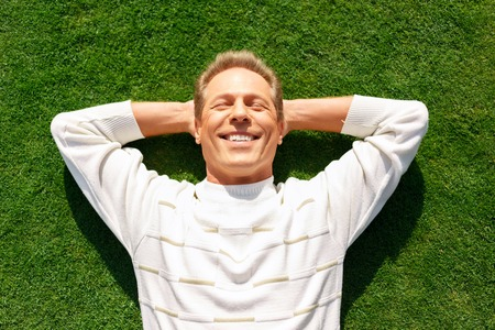 blissful: On the edge of happiness. Blissful vivacious adult man holding his hands behind the head and smiling while lying on the grass Stock Photo
