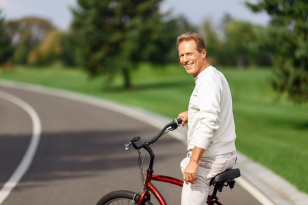 elated: Follow me. Cheerful elated pleasant handsome man smiling and riding a bicycle while resting Stock Photo