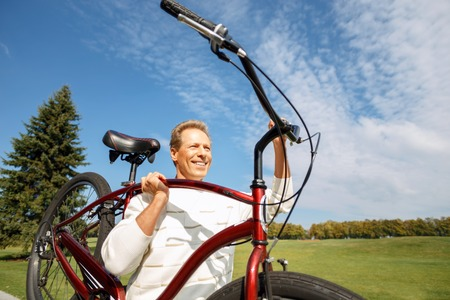 elated: Healthy and strong. Cheerful handsome agreeable man holding bicycle and smiling while feeling elated