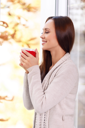 warmly: Tender moment. Attractive young girl is standing near the window with her eyes closed while holding a mug and smiling warmly.