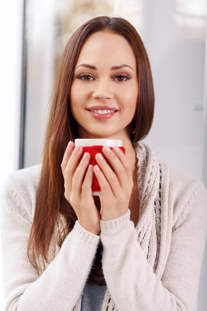 warmness: Enjoying myself. Beautiful attractive young girl smiles kindly and holds a cup of drink with both of her hands creating the feeling of safety, tenderness and warmness.