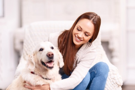 broadly: Look who is back. Attractive young lady is grinning broadly while patting and caressing her cute pet dog. Stock Photo