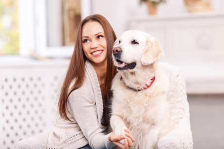 vividly: Real friendship. Young lovely girl is smiling vividly and holding her dogs paw while truly enjoying her time with the pet.