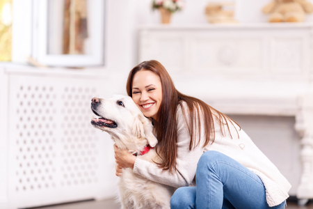 cheerfully: Moment of total happiness. Young attractive girl is laughing cheerfully while hugging her pretty cute dog.