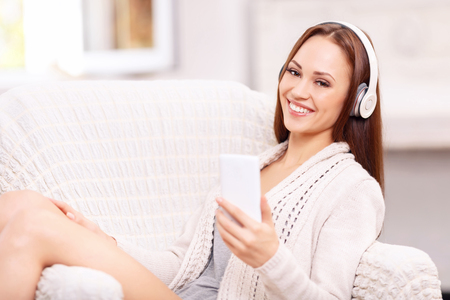 beats: Magic of sound. Cheerful young girl with sparkling eyes is laughing lightly while listening to favorite track. Stock Photo