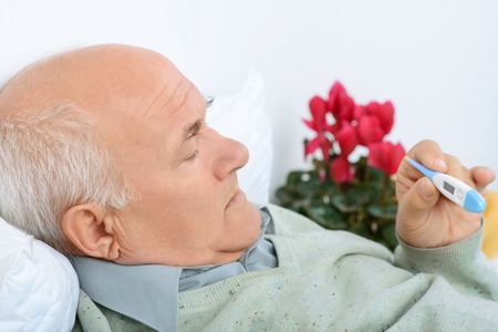 plaintive: Oh not fever again. Oppressed aged man checks his temp reader and scowls in worry.