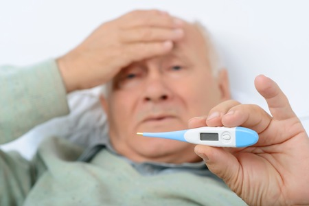 dispirited: Check my indications. Gloomy old man shows his thermometer indications while clutching at his forehead.