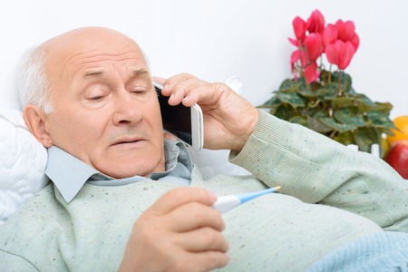 oppressed: Bad news here. Dispirited grandfather speaks on the phone about his fever and illness in general. Stock Photo