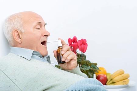 plaintive: Sore throat treatment. Senior aged man lies on hospital bed and uses his new sore throat medicine. Stock Photo