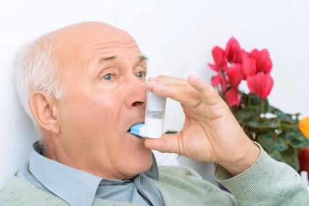 plaintive: Inhaler usage. Elderly man uses his inhaler while sitting on hospital bed.