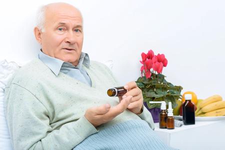 cansancio: Estos son medicamentos. El hombre mayor se sienta en su cama y sostiene p�ldoras frasco mientras hay otros remedios en el fondo.