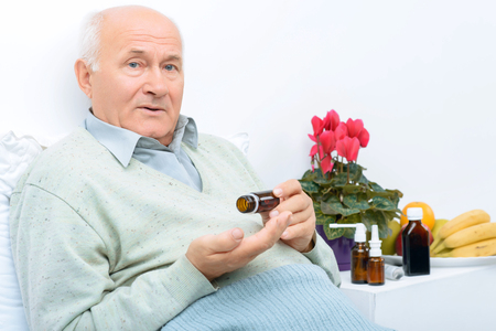 agitated: These are medicines. Elderly man sits on his bed and holds pills vial while there are other remedies on the background. Stock Photo