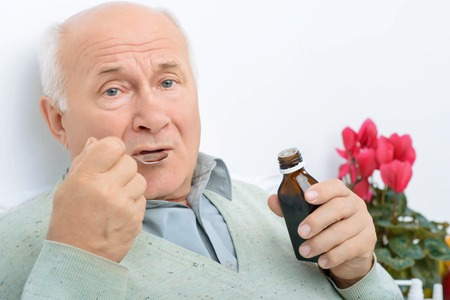 oppressed: It does not taste well. Aged patient takes in some of the cough syrup and does not look happy about it.