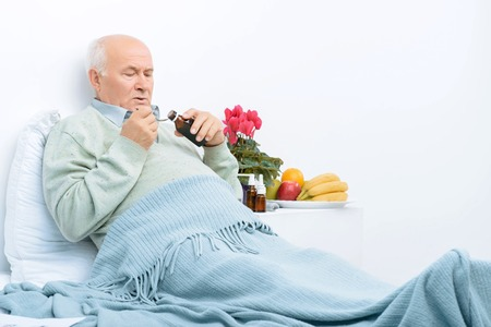 agitated: I need more syrup. Aged man lies under the blanket and decides to take cough syrup. Stock Photo