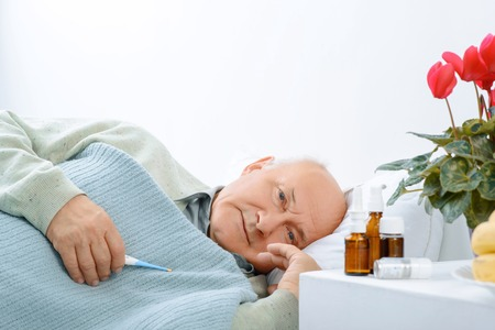 plaintive: Waiting to get cured. Elderly man covered in blanket rests on the side and holds a thermometer.