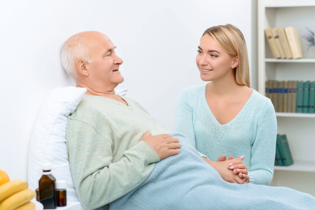 broadly: Smile is best medicine. While chatting with his relative sick grandfather feels happier and smiles broadly. Stock Photo