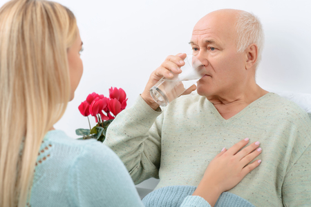 水は常に必要です。先輩患者訪問に来た彼の美しい孫娘によって与えられた水のガラスを飲みます。 写真素材
