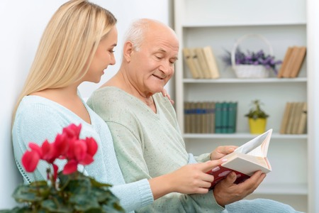 brings: Family moment. Granddaughter brings family album and shows it to her sick granddad to cheer him up. Stock Photo