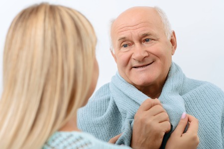 healthcare visitor: I feel warmer. Smiling grateful old man is being wrapped in blanket by his lovely granddaughter.