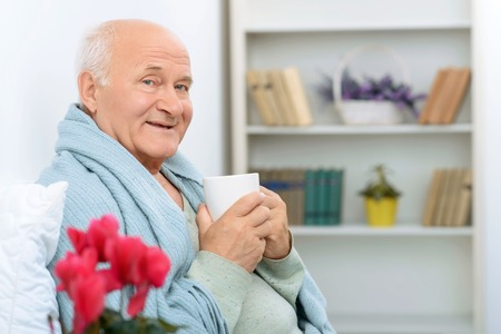 getting better: Getting better. Senior man looks more healthy and jolly while drinking tea made by his granddaughter.