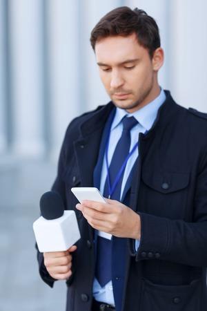 beau jeune homme: Alerte Nouvelles. Busy prospectifs homme v�rifie vivement quelque chose en utilisant son smartphone.