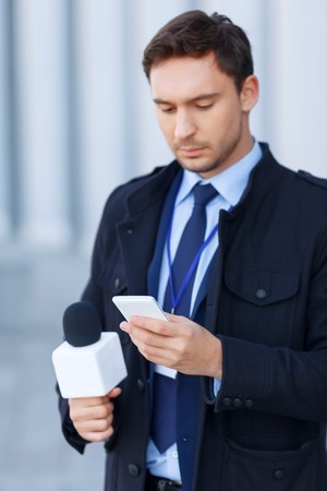 article of clothing: News alert. Busy-looking man keenly checks something by using his smartphone.