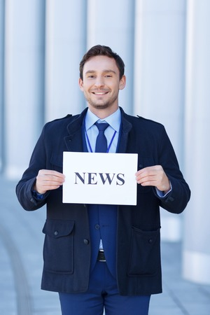 broadly: News time. Attractive young journalist grins broadly while holding titled sheet of paper.
